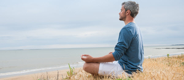 Man Sitting on Ocean Beach Meditating with Palms Up